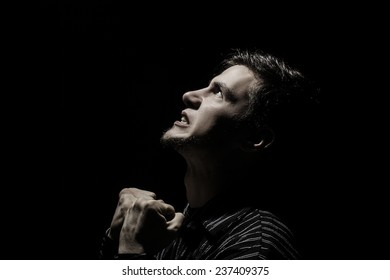 Stressed, aggressive, frustrated portrait of a young student, man,holding his fists up isolated on black background.Facial expression