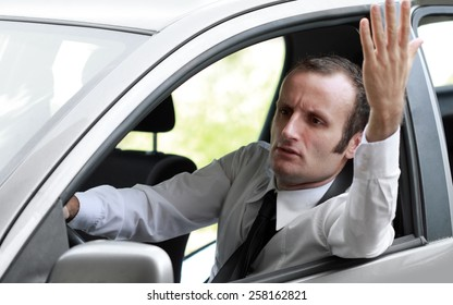 Stressed and angry businessman in a car, during the rush hour.