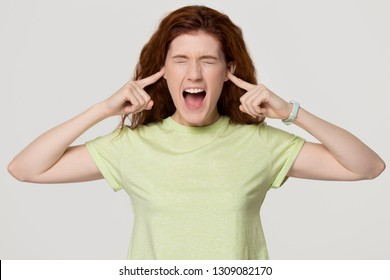 Stressed angry stubborn redhead woman sticking plug fingers in ears screaming loud feel annoyed, mad crazy rebellious red-haired teen girl yelling in tantrum isolated on white grey studio background