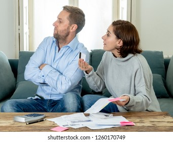 Stressed angry young couple arguing over credit card debts while accounting home finance paying bills mortgage bank statements and expenses feeling desperate in bad financial situation and bankruptcy.