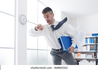 Stressed anxious businessman in a hurry checking time and running, he is late for his business appointment