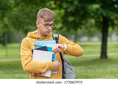 Stressed anxious young guy is late, busy university or college student or pupil with books, textbooks in glasses looking at his wrist watch, checking time in a hurry, rushing to lessons, exam. No time