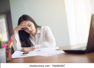 stressed Asia woman with computer in the office.