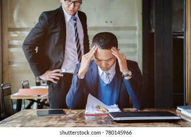stressed asian business man working with laptop on desk, boss/manager do angry face complaining standing behind employee, business co-working unhappy teamwork concept
