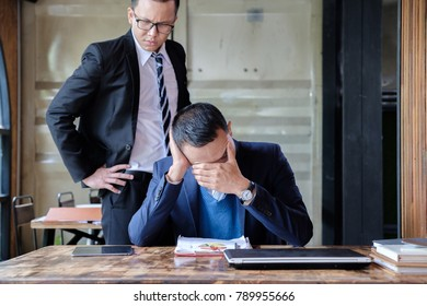 stressed asian business man working with document on desk, boss/manager do angry face complaining standing behind employee, business co-working unhappy teamwork concept