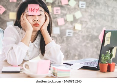 stressed Asian business woman tired from overworked sitting at office desk with note on face