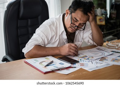 Stressed asian businessman holding a glass of whiskey and smoking. he sleep on the money, data charts, business document at office desk.  alcohol addiction - drunk businessman concept