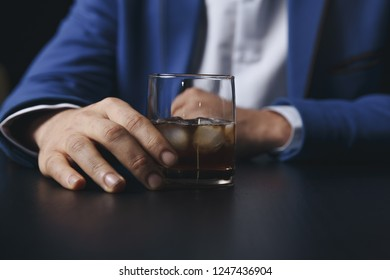 Stressed asian businessman holding a glass of whiskey he sleeping and Data Charts,business document at office desk. alcohol addiction - drunk businessman concept