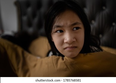 Stressed asian child girl suffering nightmare,waking up at night on her bed in the dark bedroom,flinch,shudder,startled from a nightmare,terrified woman from horror bad dream,problem lifestyle concept
