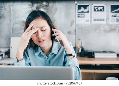 Stressed Asian creative designer woman cover her face with hand and feel upset while talk on mobile phone with customer in front of laptop computer on desk at office,Stress office lifestyle concept.