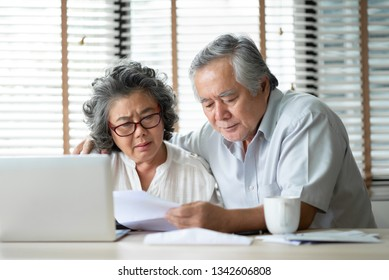 Stressed Asian Elderly Couple calculate their monthly expense with laptop computer on desk in the house. Worried Senior man and woman having problem about Debts. Saving, Financials with Retirement.