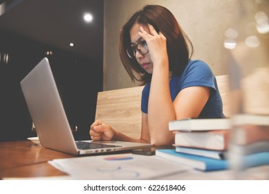 Stressed of Asian eyeglasses Woman with laptop and graph financial diagram documents on wooden table. Headache and migraine.