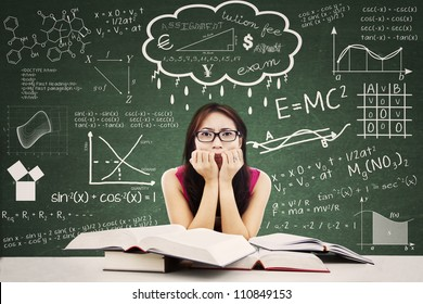 Stressed Asian student in a classroom. Shot against blackboard with formula from many different subjects