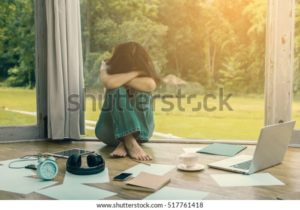 Stressed asian woman with frustrated, overworked at home and near the girl is alarm clock, book, tablet, headphones and background blur beautiful garden at home. (vintage color tone, lens blur effect)