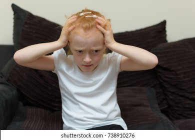 Stressed autistic young girl holding her hand to her ears whilst having a meltdown whilst sitting on a brown sofa in a hot me environment