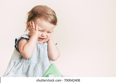 Stressed baby girl covering her ears with hands, not listening at light background