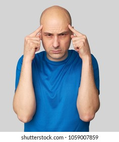 stressed bald man serious thinking, holding head with hands. Isolated on grey background