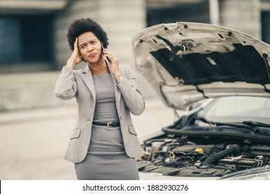 Stressed black business woman calling roadside assistance after her car broke down.