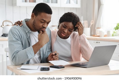 Stressed Black Couple Calculating Family Budget In Kitchen. Young African American Spouses Suffering Financial Crisis, Checking Monthly Expenses And Tax Bills Together At Home, Having Debts