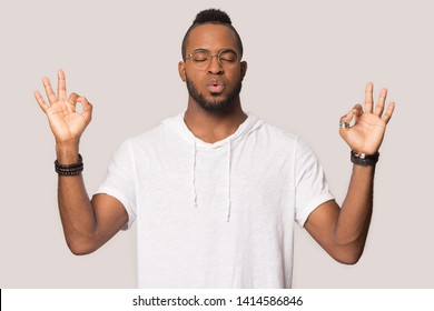 Stressed black guy meditating pose isolated on beige studio background, mixed race man in glasses folded fingers mudra symbol exhales and calms down breathing deep, self control, stress relief concept