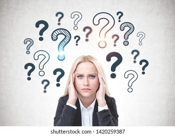 Stressed blonde woman in suit sitting near concrete wall with question marks drawn on it. Concept of looking for anwer