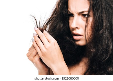 stressed brunette woman looking at damaged dry hair isolated on white