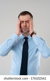 Stressed business man with headache isolated on grey background