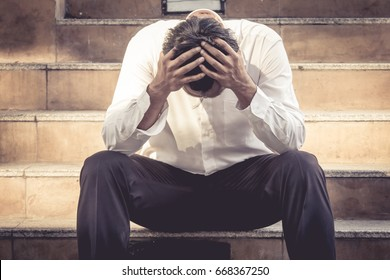 Stressed business man sitting with hand on head