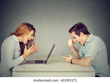 Stressed business woman with laptop sitting at table with angry man screaming at mobile phone. Negative emotions in office life