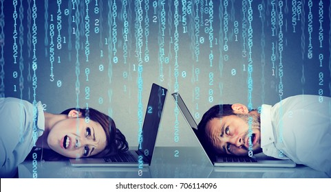 Stressed business woman and man resting head on laptop under binary code rain sitting at table frustrated with each other