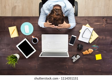 Stressed business woman sitting at office table and holding head in hands. Shot from above.