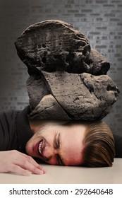 Stressed businessman banging his head against dark grey room