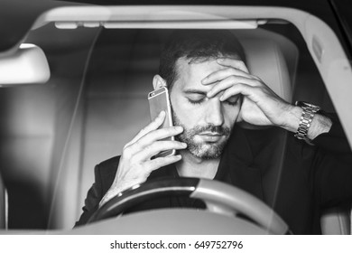 Stressed businessman calling on a mobile phone in the car.
