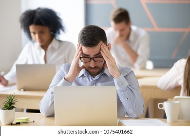 Stressed businessman concerned about hard online task looking at laptop in shared office, frustrated worried male employee reading news, tired exhausted office worker feeling headache at work