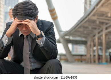 Stressed businessman Feeling sick and tired while sitting at stairway outdoor. Bankrupt businessman sitting outdoor feeling stress and unhappy. Feeling stress from the lost of job and businesses.