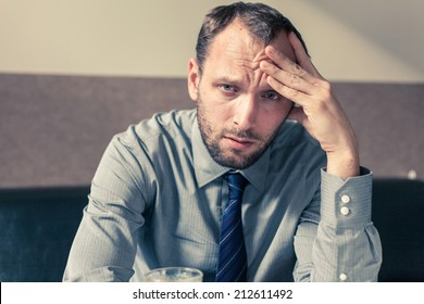 Stressed businessman getting a headache at home in the living room.