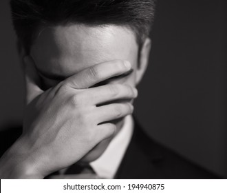 Stressed businessman with hand over his face. Unrecognizable person.