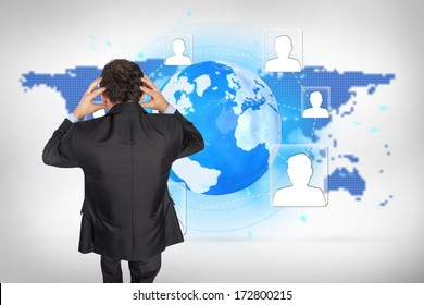 Stressed businessman with hands on head against blue world map on white background