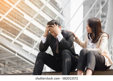 Stressed businessman has problem  and gilfriend consoling  with  city background.Unhappy businessman being sad and sitting with girlfriend outdoor.