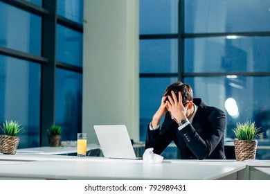 Stressed businessman having problems and headache at work sitting with laptop