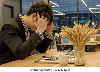 Stressed businessman with his head in hands at his table office place