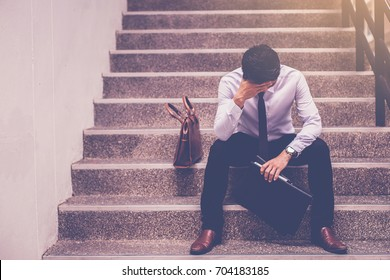 stressed businessman holding portfolio sitting at stairway. disappointed for job search