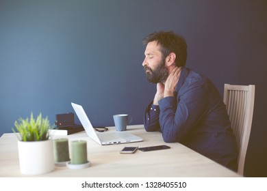 Stressed businessman with laptop computer on wooden table sitting at home,dealing with a neck ache