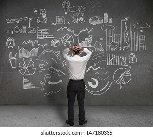 Stressed businessman looking at drawings of charts and sketches on a wall
