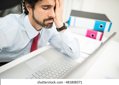 Stressed businessman looking at his computer