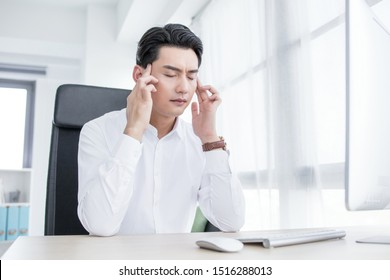 Stressed businessman with a migraine headache sitting at his desk rubbing his temples with his fingers with his eyes screwed shut in pain