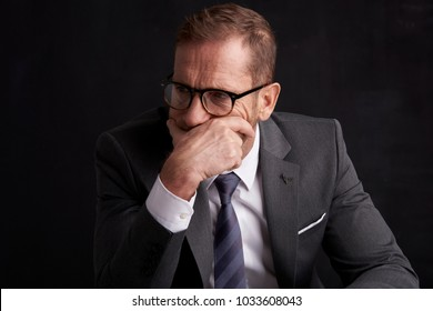 Stressed businessman mouth is covered with his hands while sitting at dark background and thinking very hard. Professional man wearing suit.