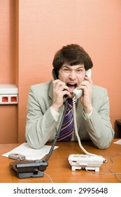 A stressed businessman shouting on the phones