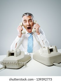 A stressed businessman shouts into the two handsets that he is holding.