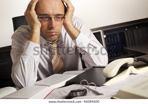 Stressed businessman sitting at desk in office being overloaded with loads of work